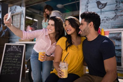 Happy friends taking selfie from mobile phone in food truck van