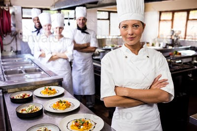 Female chef standing with arms crossed in kitchen at hotel