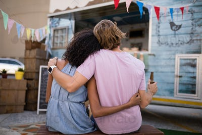 Rear view of romantic couple sitting with beer bottle near food truck