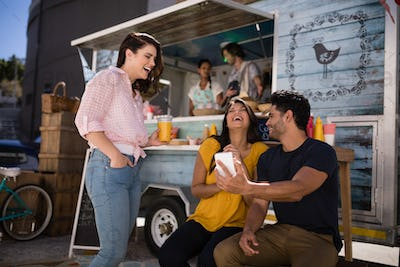 Friends looking at mobile phone and smiling in food truck van