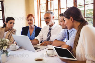Business people discussing over laptop at table in restaurant