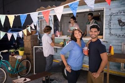 Portrait of happy couple standing with juice