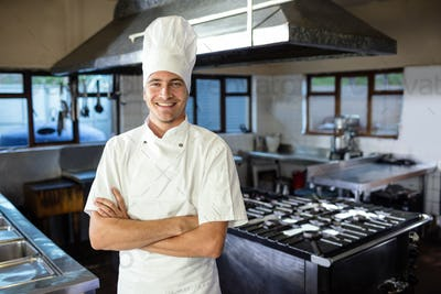 Male chef standing with arms crossed in kitchen at hotel