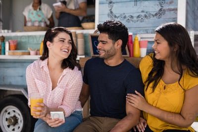 Smiling friends interacting with each other in food truck van
