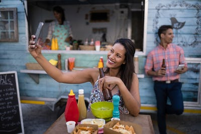 Beautiful woman taking selfie from mobile phone in cafeteria