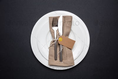 Table place setting with linen napkin and blank tag on black color background