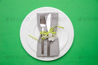 Table place setting in bright green. Gray linen napkin and white plates on green color background