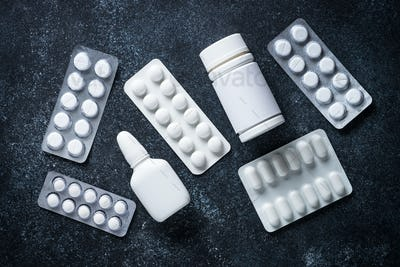 Tablets and medicines on a black top view.