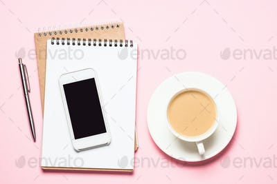 Home Office workplace with notepad, smartphone and coffee cup on pink desk.