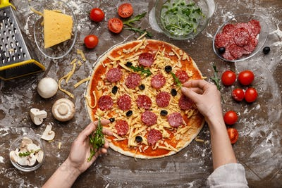 Chef adding rocket salad to pizza, top view