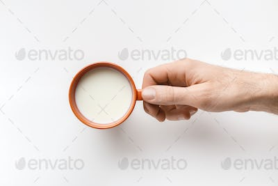 Man's hand with cup of milk