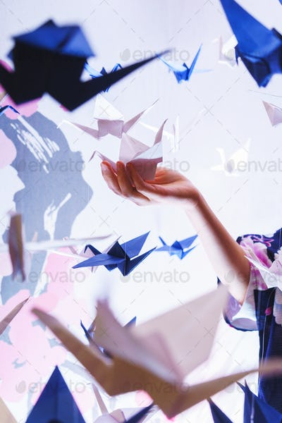 Girl holding a traditional Japanese origami swan made out of pap