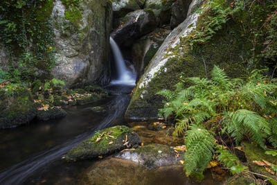 A stream jumps and forms cascades between granite rocks