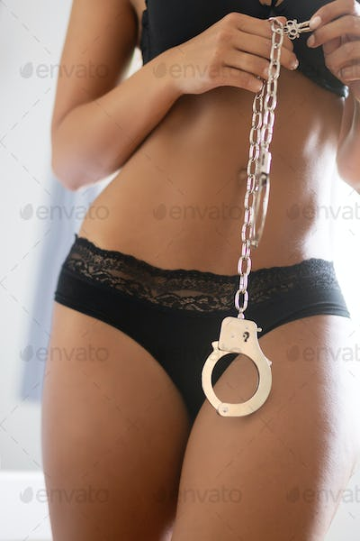 Sexy beautiful woman holding handcuffs in lingerie