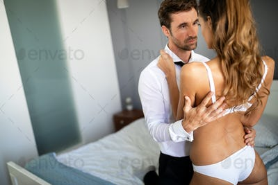 Beautiful woman and handsome muscular man close to each other in erotic pose.