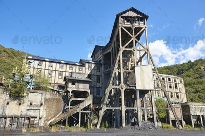 Abandoned coal factory. Industrial rusted machinery. Polluted landscape. Renewable energy