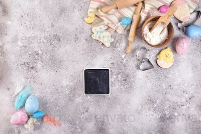 Baking accessories on stone background with flour, eggs and easter glazed cookies