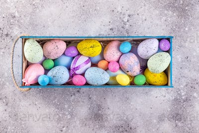 easter colorful eggs painted in bright colors with straw nest in wooden box on stone background