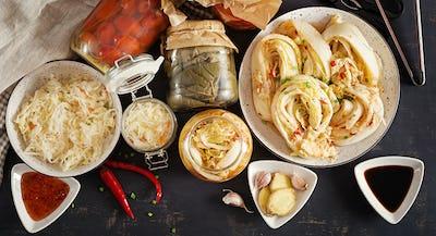 Cabbage kimchi, tomatoes marinated, sauerkraut sour glass jars over rustic kitchen table.