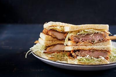 Katsu Sando - food trend japanese sandwich with breaded pork chop, cabbage and tonkatsu sauce.