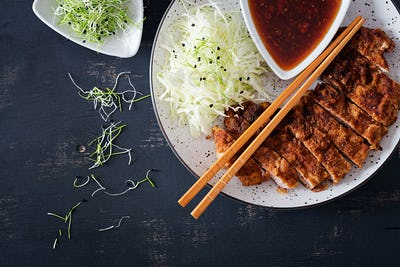 Japanese cuisine. Deep-fried pork chop, or Japanese chop with cabbage and tonkatsu sauce. Top view