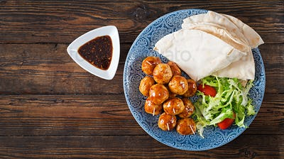 Meatballs in sweet and sour glaze on a plate with pita bread and vegetables in a Moroccan style