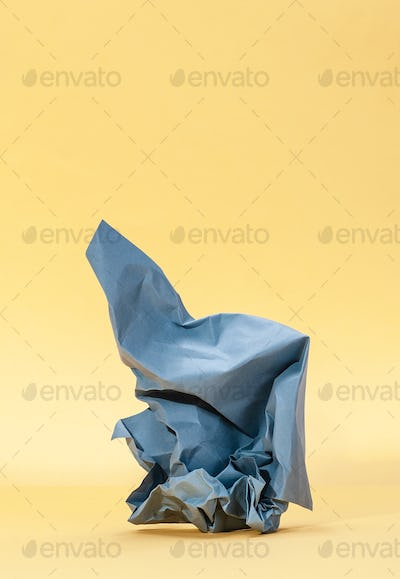 Crumpled blue paper on a pastel yellow background.