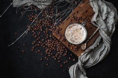 Coffee with milk foam on a dark background. Low key photography.