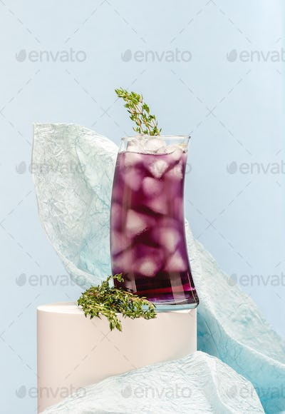 Cold cocktail with ice in a tall glass on a light blue backgroun