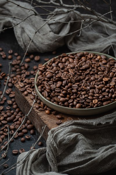 Coffee beans in a plate on a wooden stand. Low key photography c