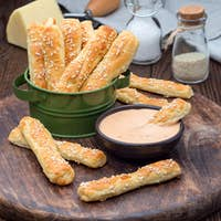 Homemade savory bread sticks with cheese and sesame in a basket,