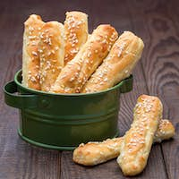 Homemade savory bread sticks with cheese and sesame on wooden ta