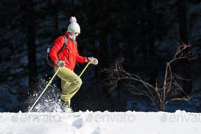 A woman takes a snowshoe trip