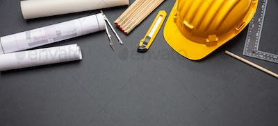 Project blueprints, yellow hardhat and engineering tools on black