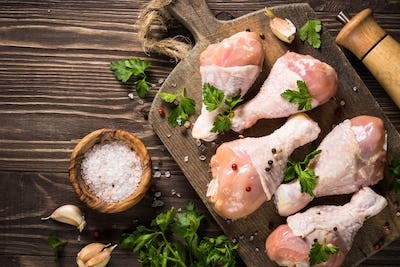 Chicken legs or drumctick on cutting board.