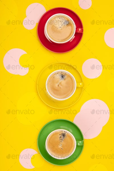 Cups of Coffee and colorful paper circles on yellow paper backgr