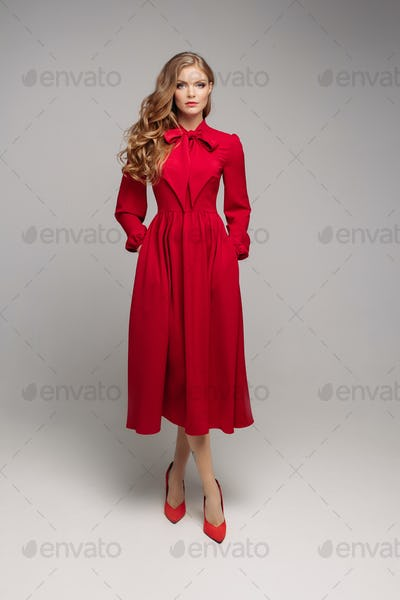 Stunning slim model in bright red dress and black heels.