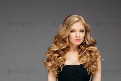 Stunning blonde woman with hairstyle after hairdresser's looking