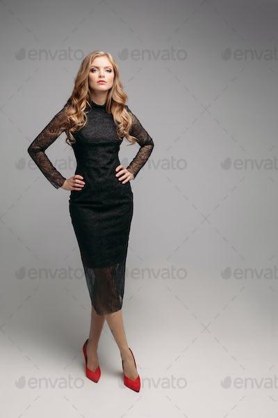 Gorgeous blonde woman in elegant black dress smiling at camera.