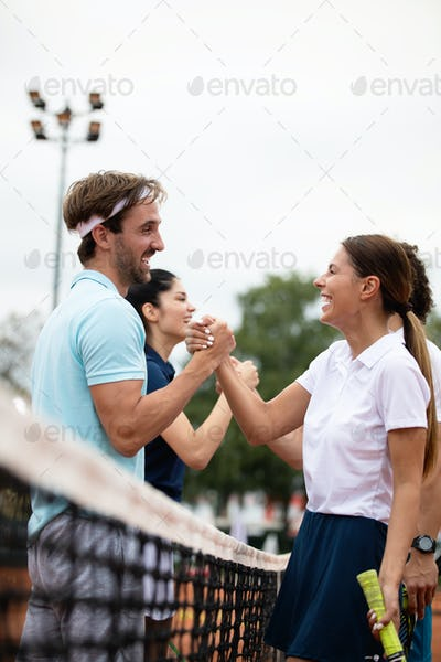 Happy group of tennis players at the tennis court
