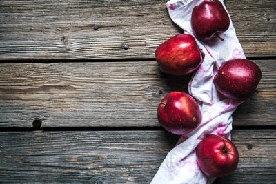 red apples and a kitchen towel on wooden background. fruit, natural food