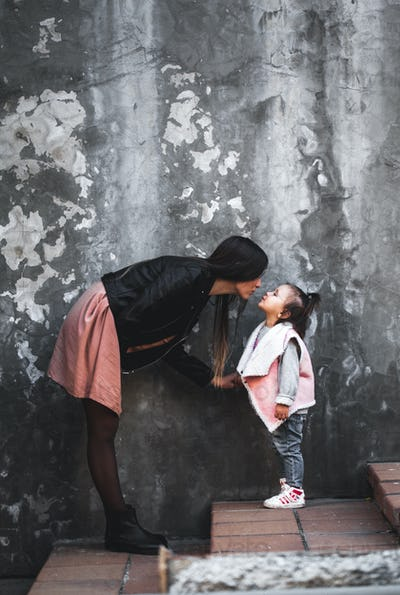 Young beautiful mom with her daughter wearing stylish clothes on a gray background