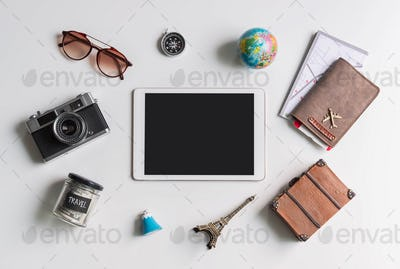 Empty screen tablet with travel accessories and items