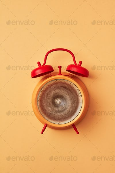 Retro style yellow alarm clock with red bells and fresh coffee instead of dial-plate on an yellow