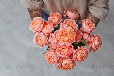 Beautiful bouquet of fresh roses in woman's hands with tatoo in a color of the year 2019 Living