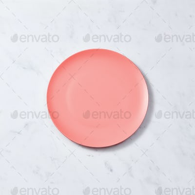 Porcelain handmade empty plate in a color of the year 2019 Living Coral pantone on a gray marble