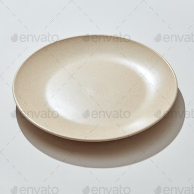 Porcelain handmade empty plate in a pastel color on a gray background with shadows