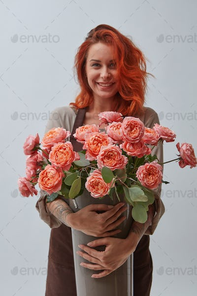 Young woman with a big vase of roses flowers in a color of the year 2019 Living Coral Pantone on a