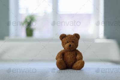 Plush teddy bear toy on white bed
