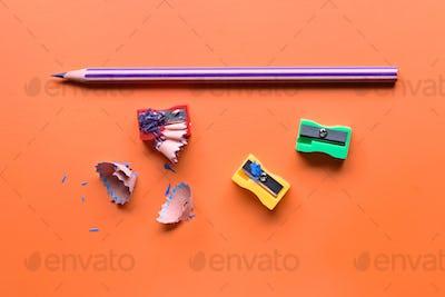 colored pencils and pencil sharpener on orange board